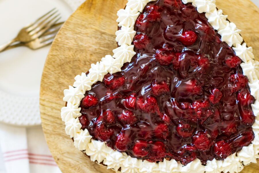 Heart shaped chocolate cake with cream filling and topped with cherry pie filling on a wooden cake stand.